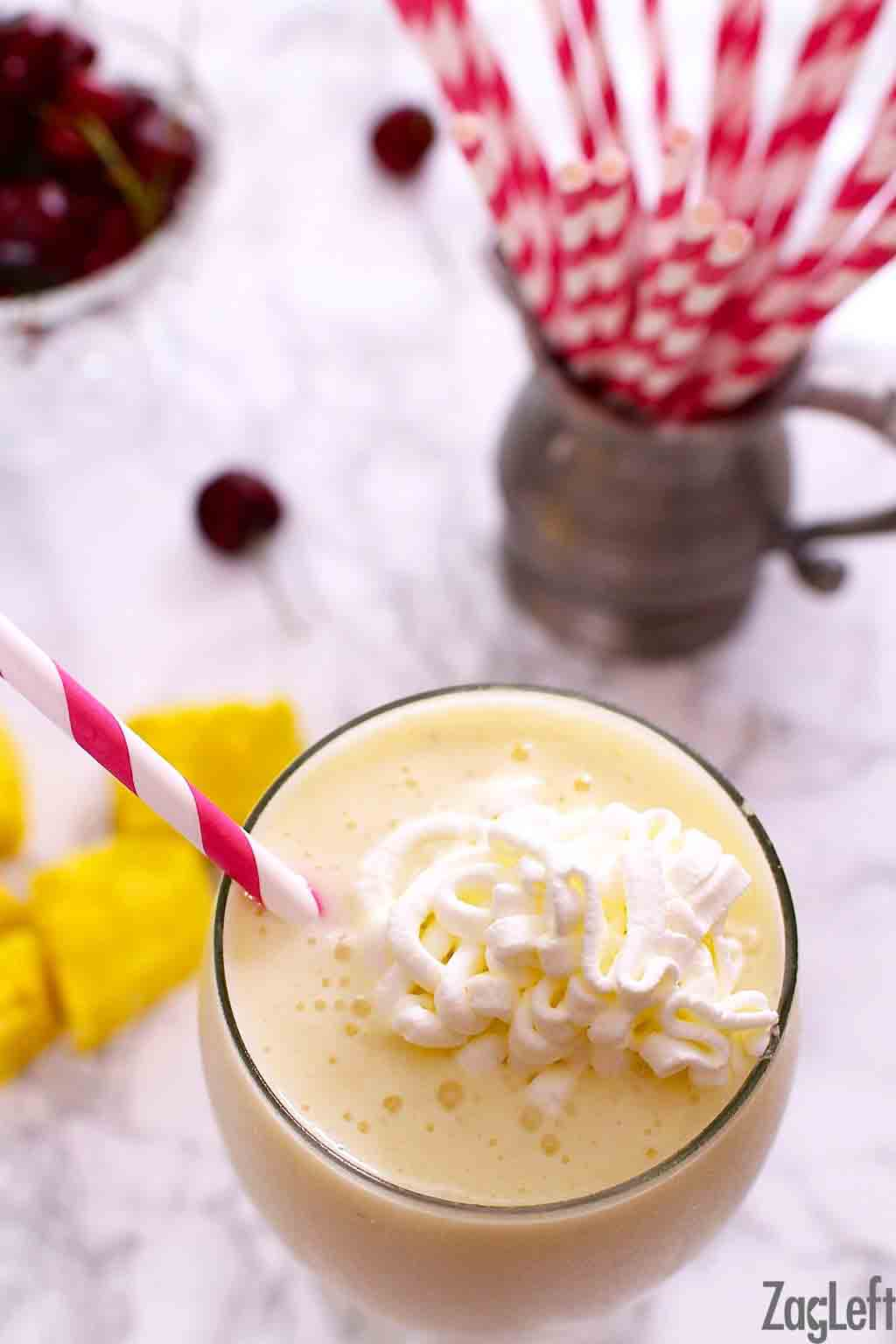 An overhead view of a smoothie topped with whipped cream next to a metal jar of red and white straws and a a few sliced pineapple pieces