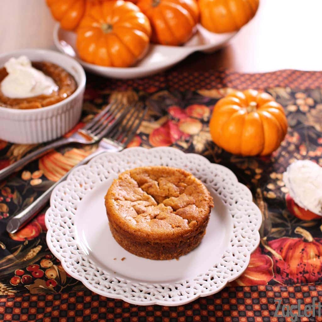 A mini pumpkin pie plated on a fall themed tablecloth with another mini pumpkin pie in a ramekin topped with whipped cream and small pumpkins in the background