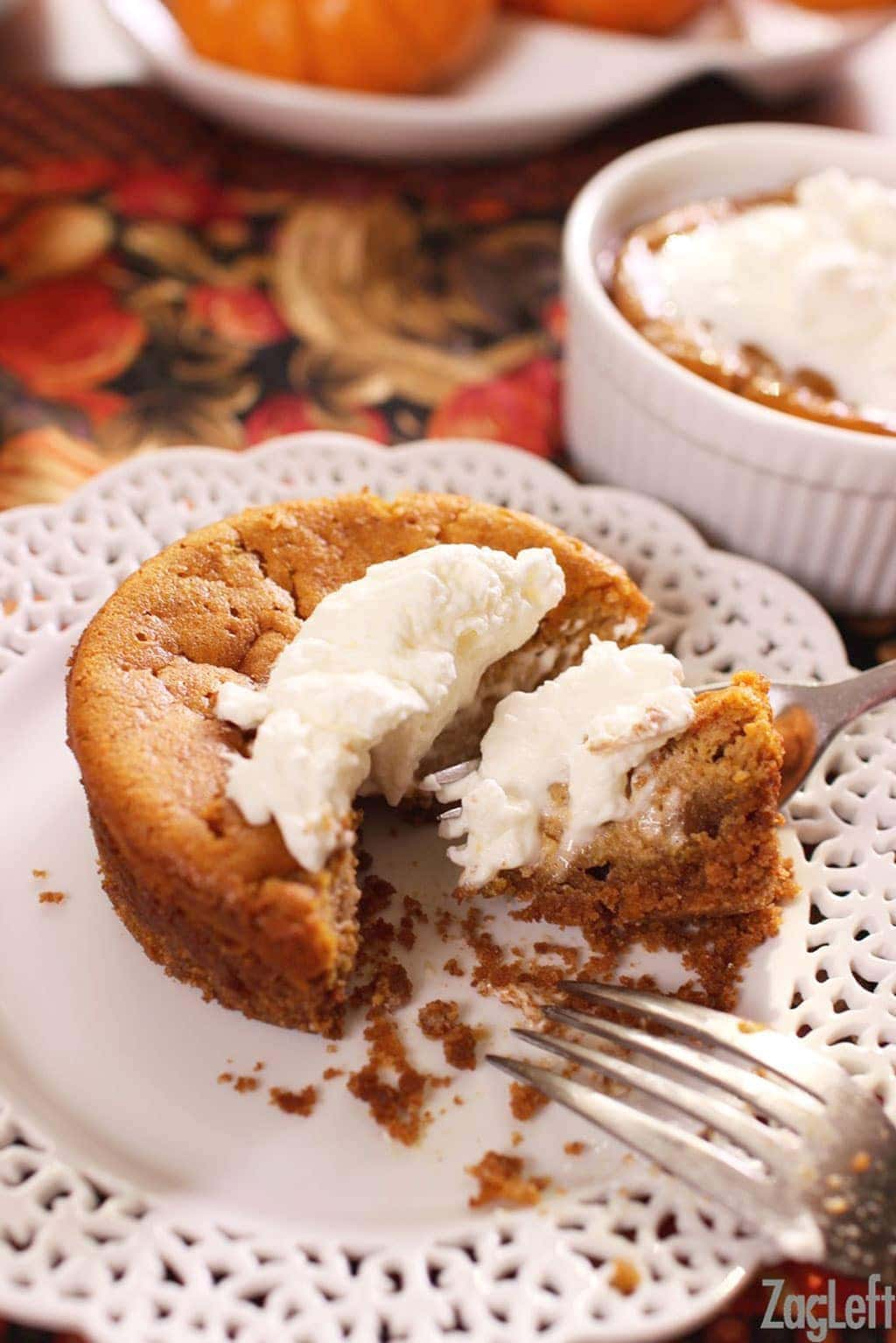 A forkful of pumpkin pie topped with whipped cream on a plate and another pumpkin pie in a ramekin topped with whipped cream in the background