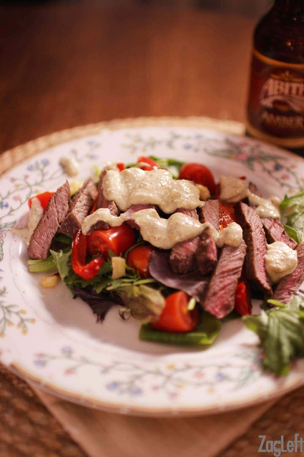 A plate of steak salad with gorgonzola dressing next to a beer bottle