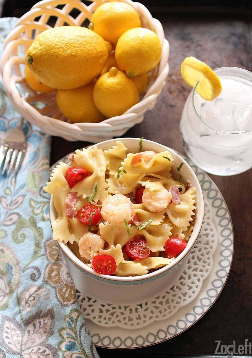 An overhead view of shrimp and prosciutto pasta in a small bowl plated on a metal tray with a small bowl of lemons and a glass of ice water