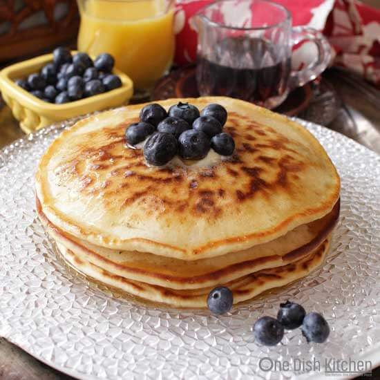 Stack of three pancakes with blueberry and melted butter