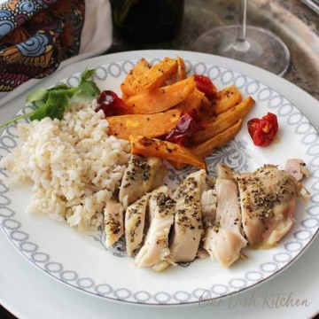 sheet pan chicken cut up with rice and carrot slices on white plate