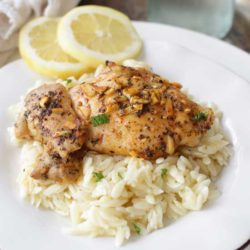 lemon garlic chicken on a bed of rice on a white plate