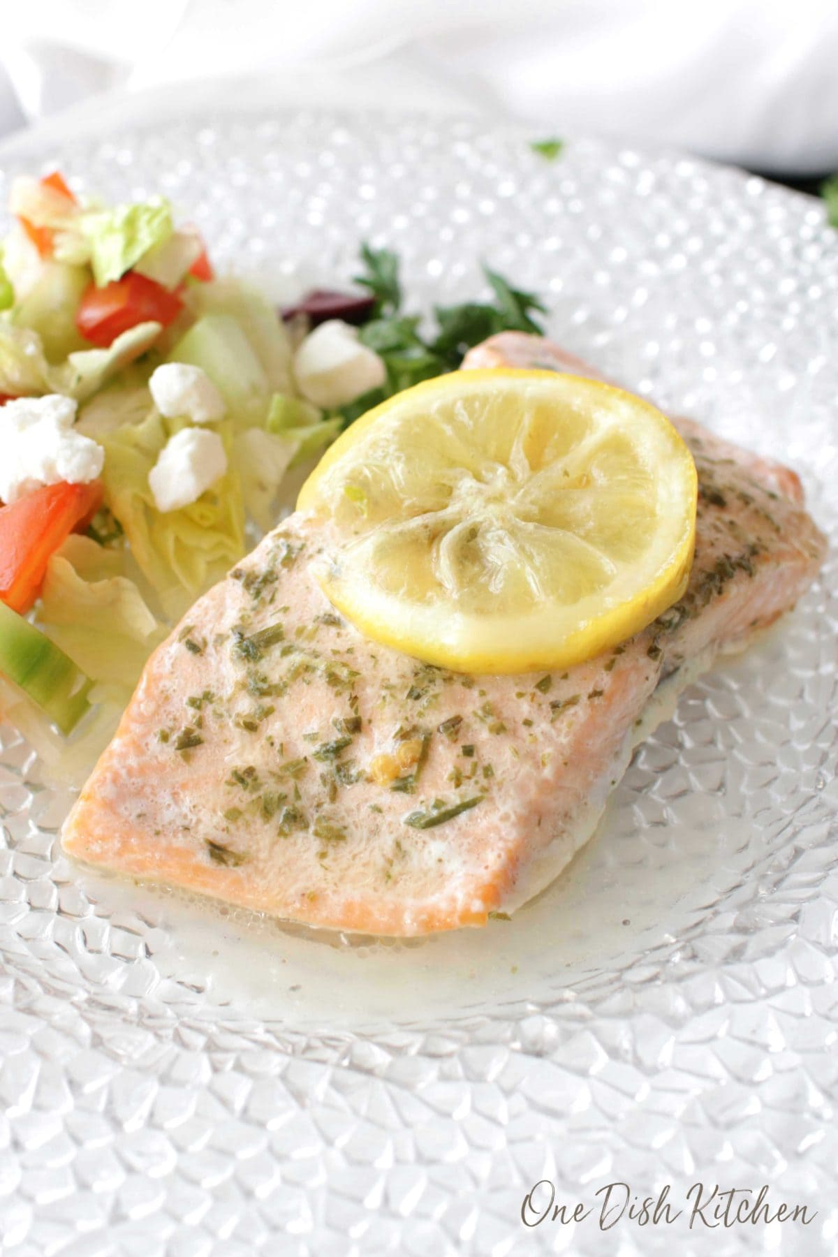 a piece of salmon that was baked in foil on a white plate topped with a lemon slice next to a salad