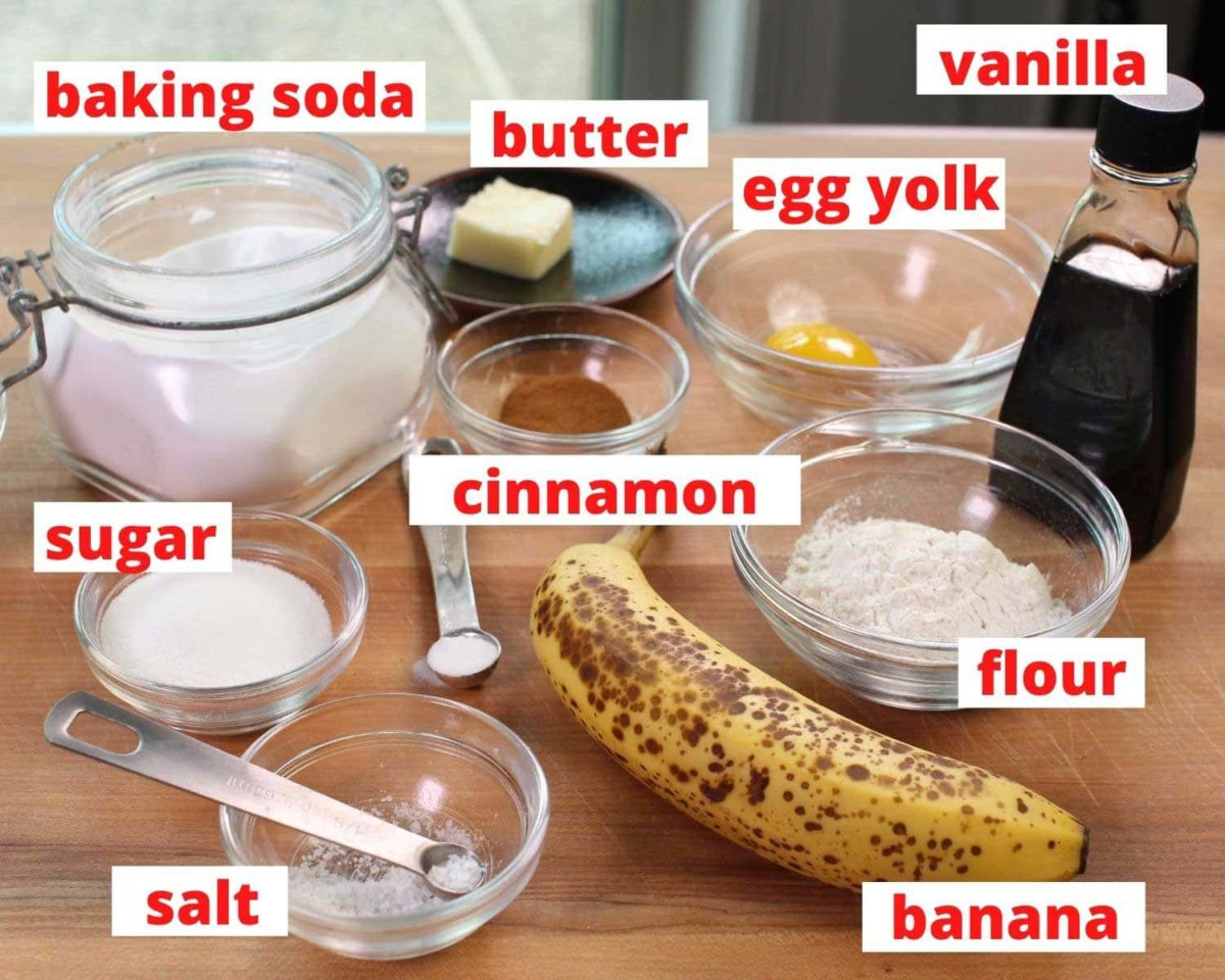 the ingredients used to make banana bread labeled and placed on a brown wooden cutting board.