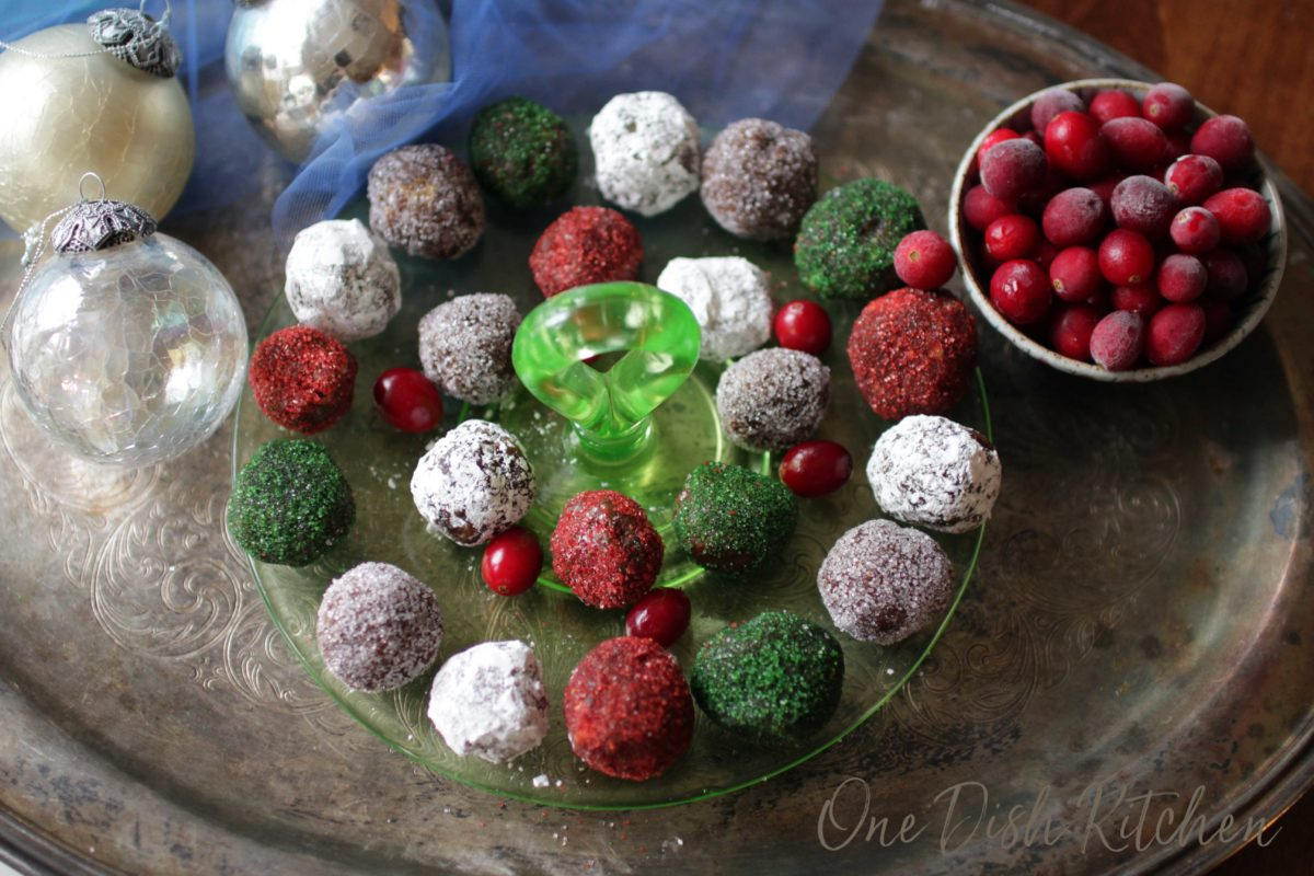 an overhead picture of a plate of red, green and white sugar plums surrounded by fresh cranberries and silver christmas ornaments.