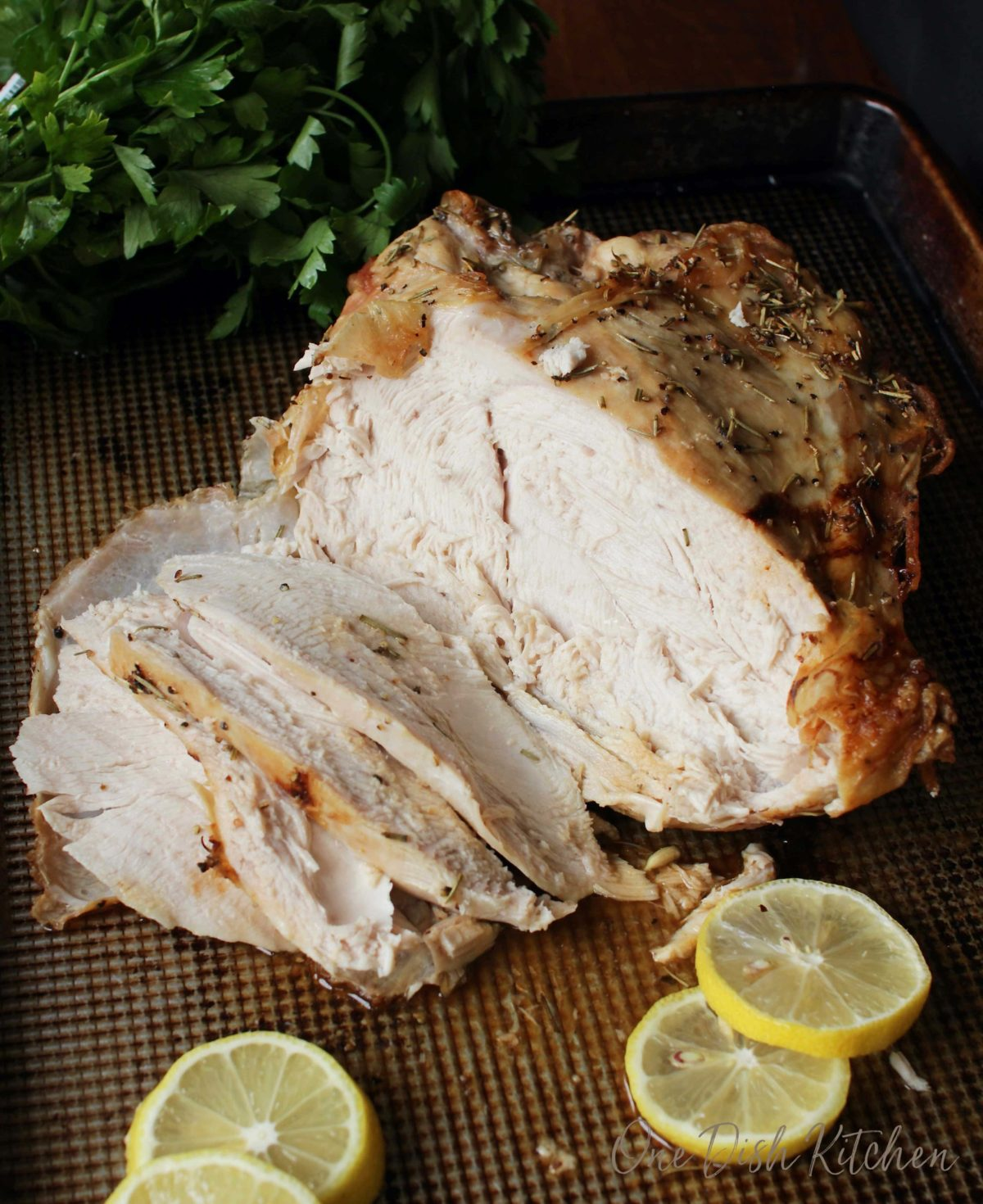 Roast turkey breast cut into slices on a baking dish with four lemon wheels
