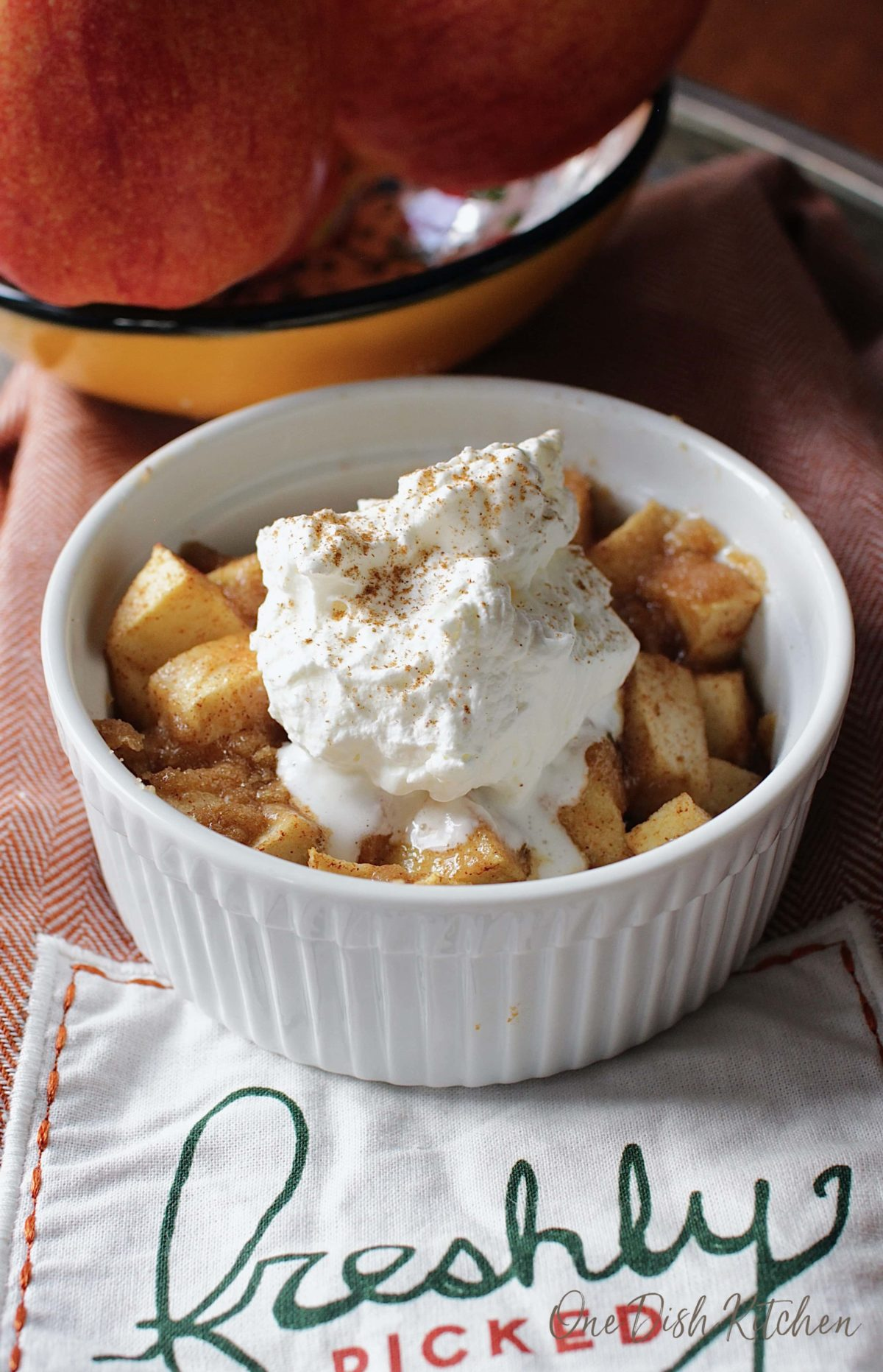 Apple crisp in a ramekin topped with whipped cream and dusted with cinnamon