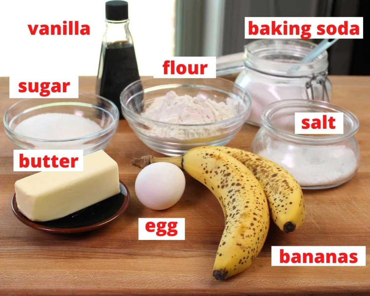 the ingredients used in banana muffins on a brown wooden cutting board.