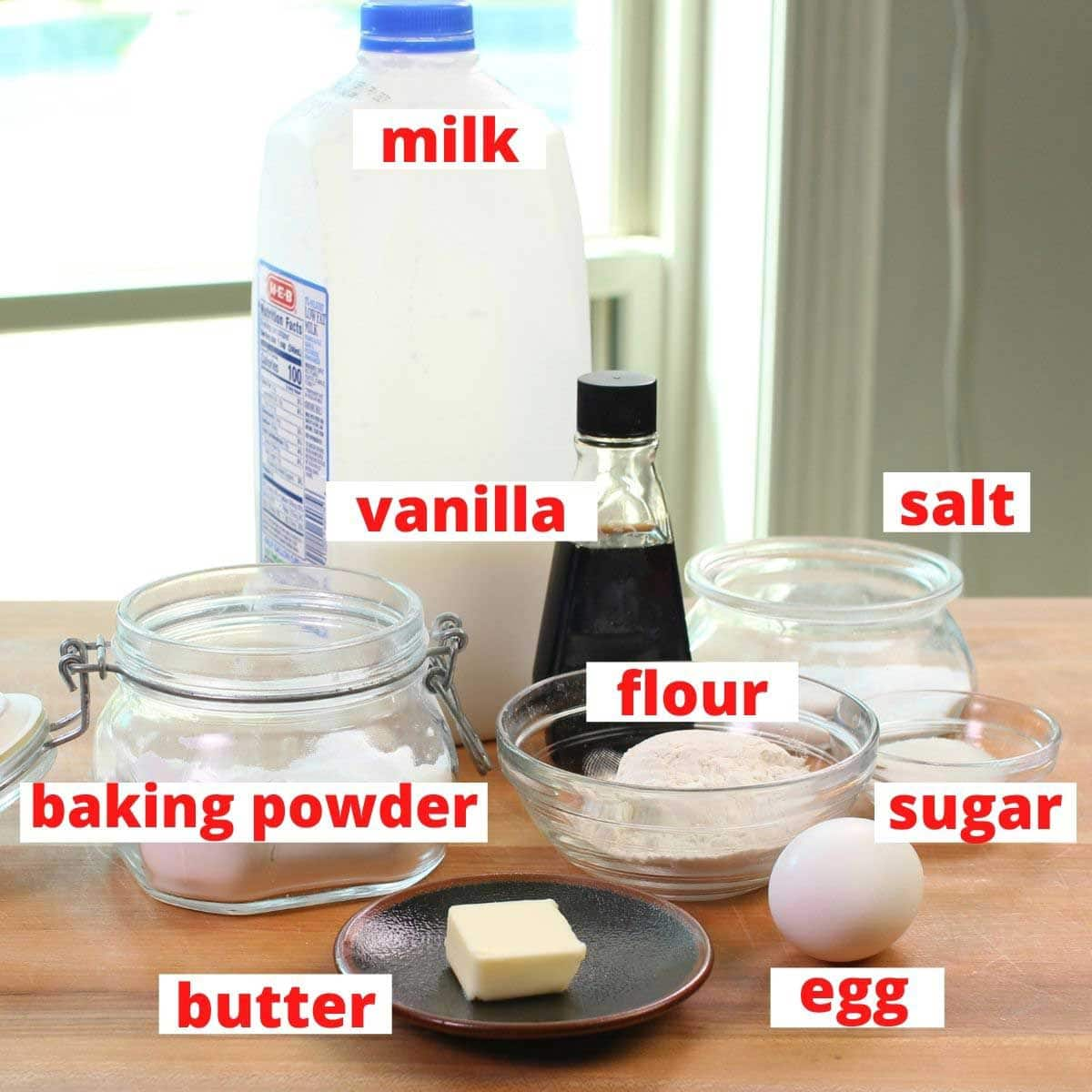 the ingredients needed for making waffles labeled and on a brown table.