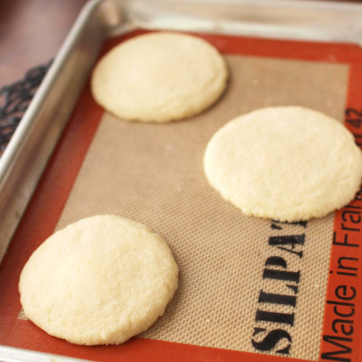 cookies with sugar sprinkled over the top on a silpat liner.