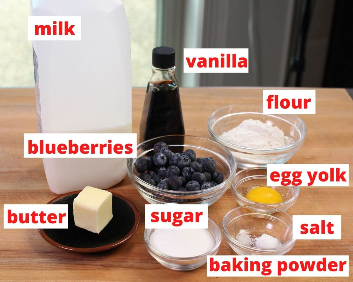 ingredients in blueberry muffins including flour, egg, sugar, and blueberries on a brown table.