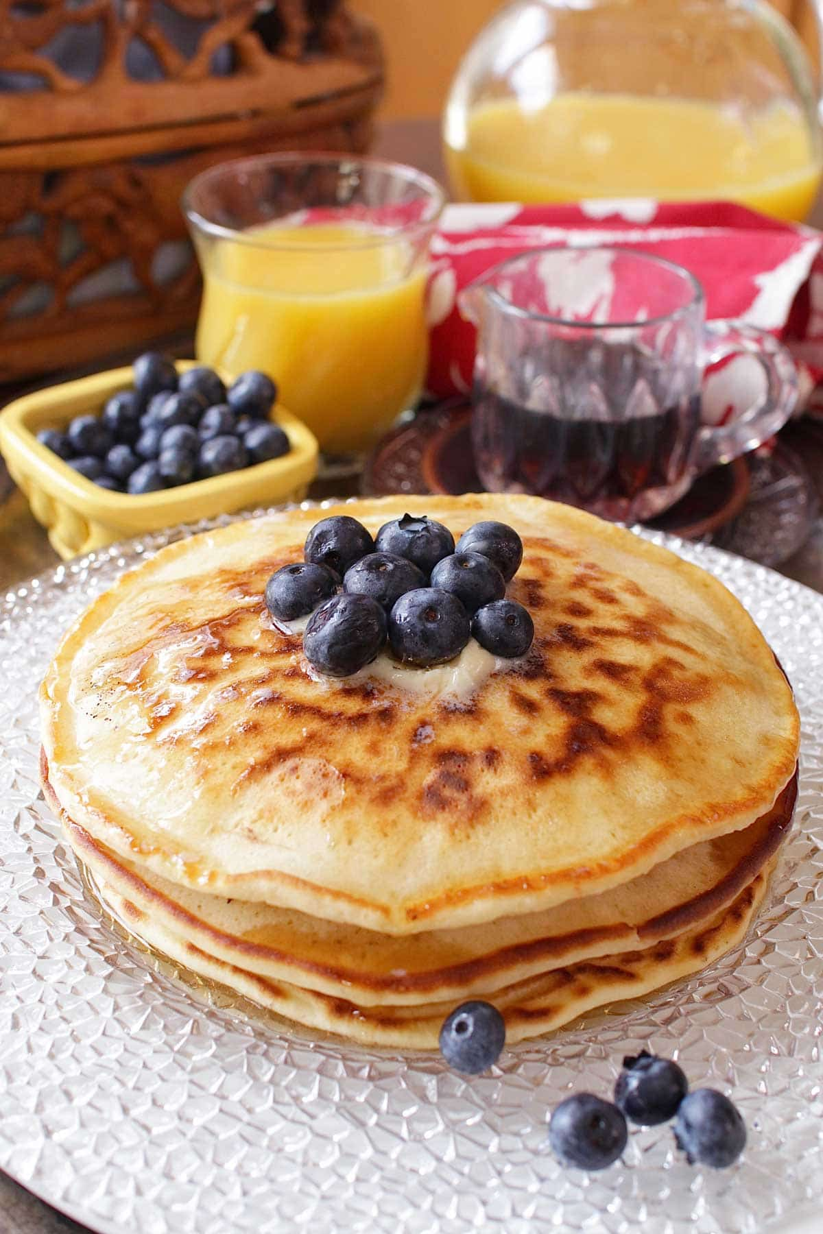 Three pancakes stacked on a plate and topped with melted butter and blueberries.