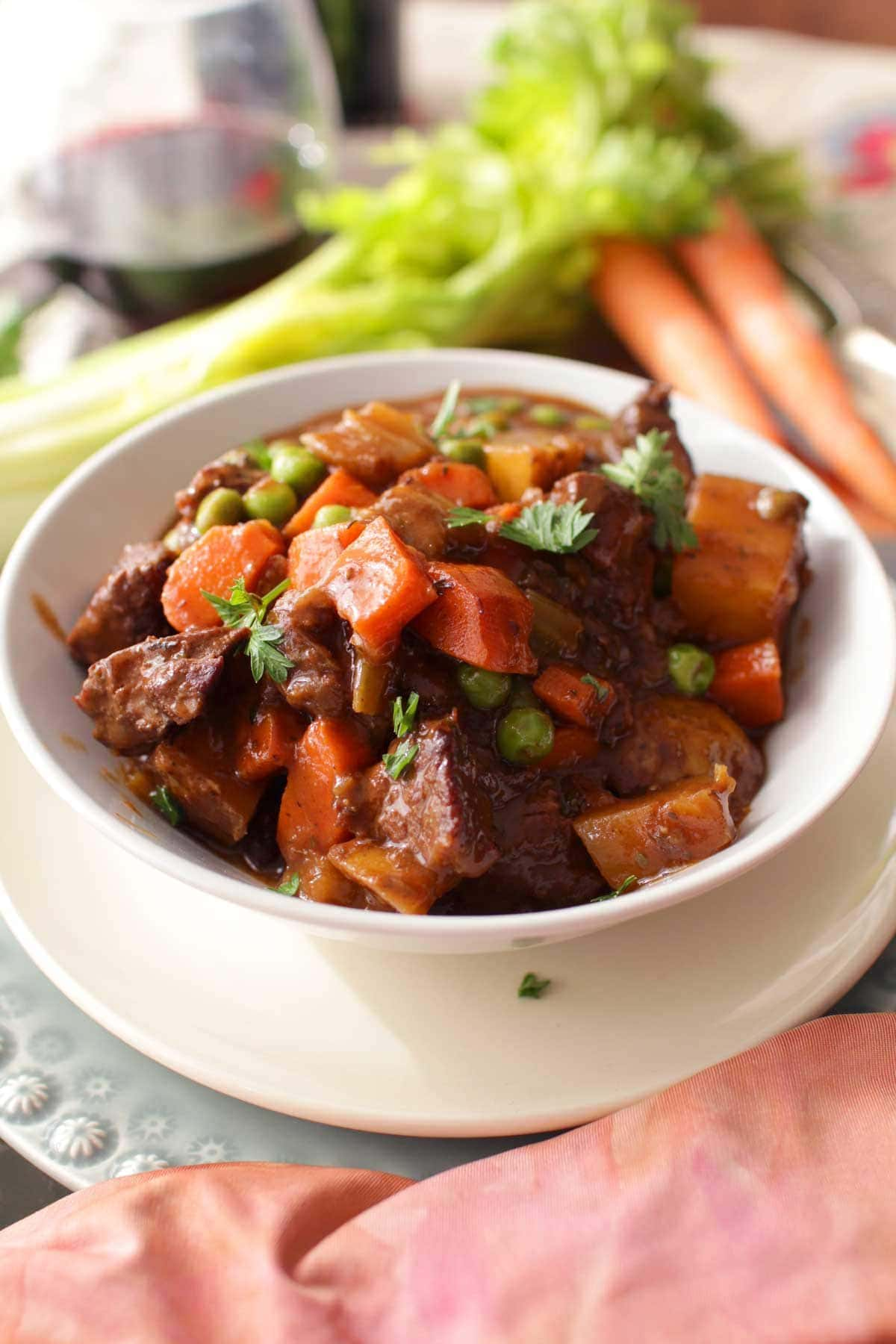 Beef stew in a bowl on a metal tray next to two carrots, a stalk of celery, and a glass of red wine