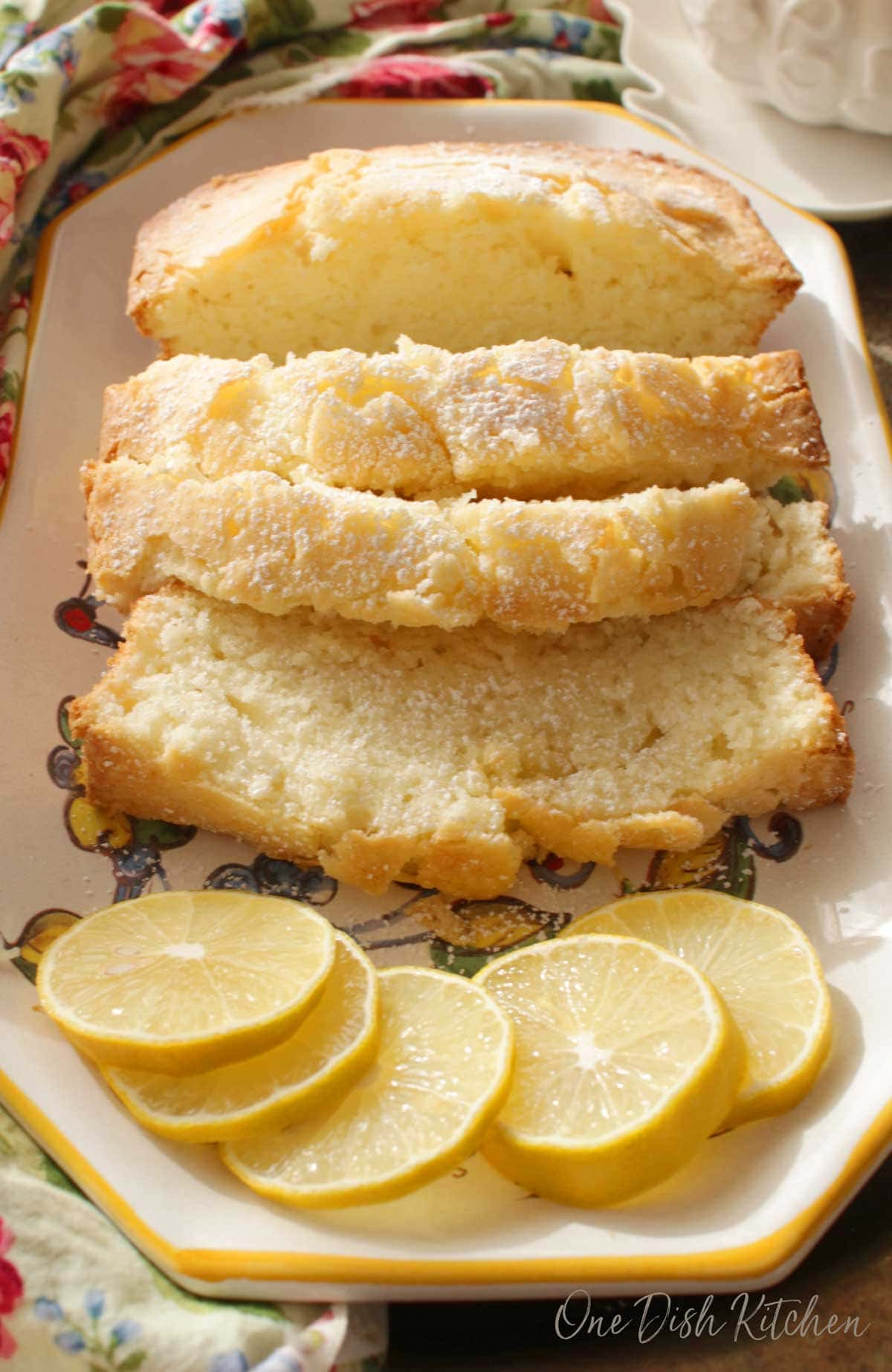 Four slices of pound cake dusted with powdered sugar on a plate with five decorative lemon wheels