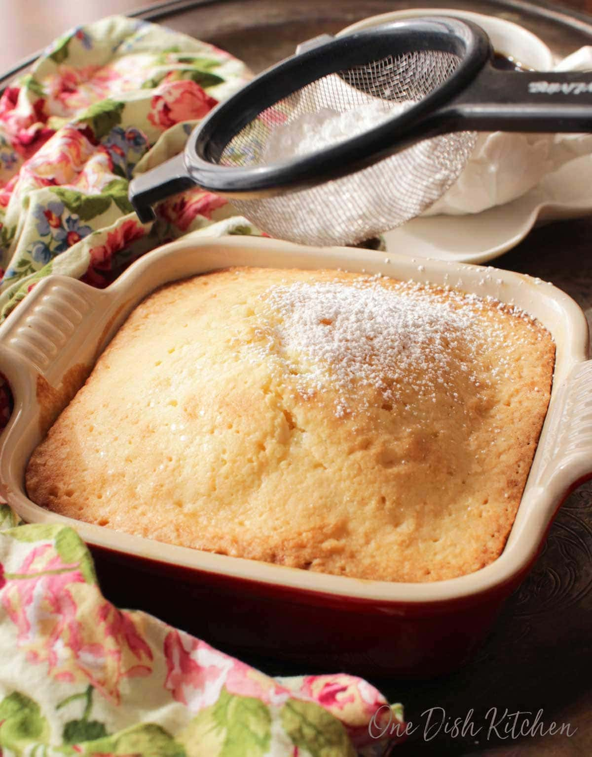 One square pound cake in a small baking dish being dusted with powdered sugar next to a cup of coffee.