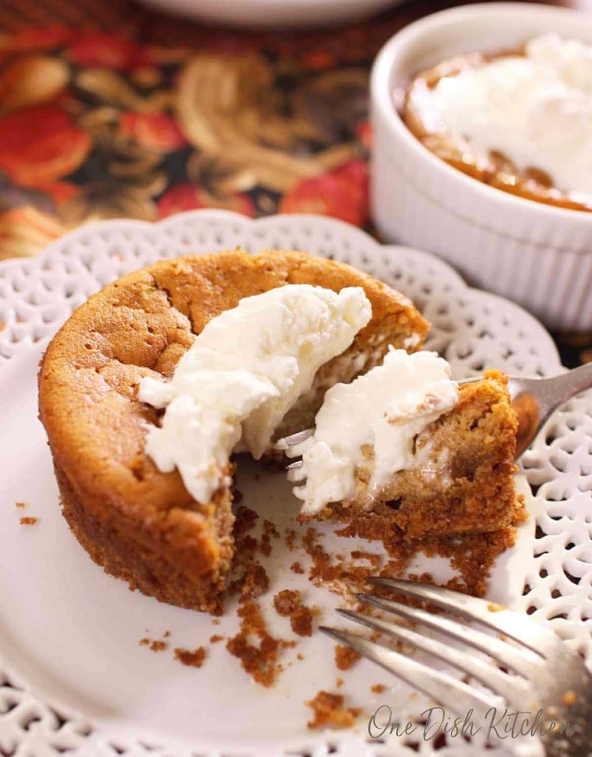 a small round pumpkin pie topped with whipped cream on a white lace plate on top of a orange and gold tablecloth.