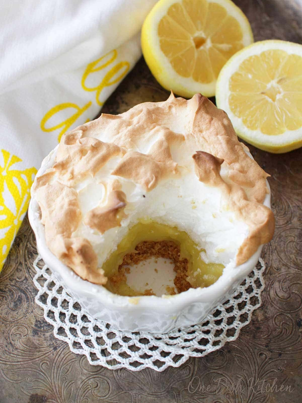 A small round lemon meringue pie with a round section removed next to sliced lemons on a silver tray.
