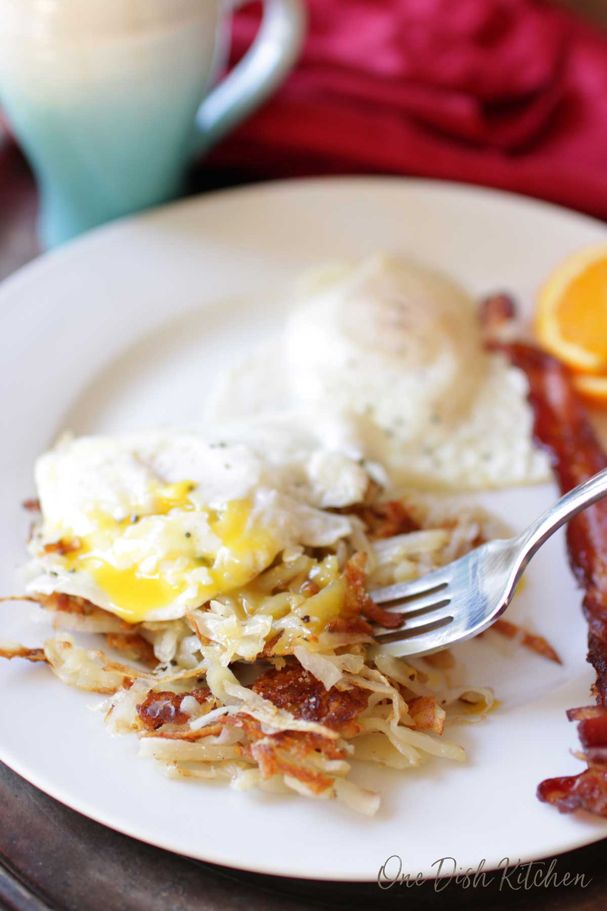 A forkful of hash browns and runny eggs from a plate with slices of bacon and orange slices