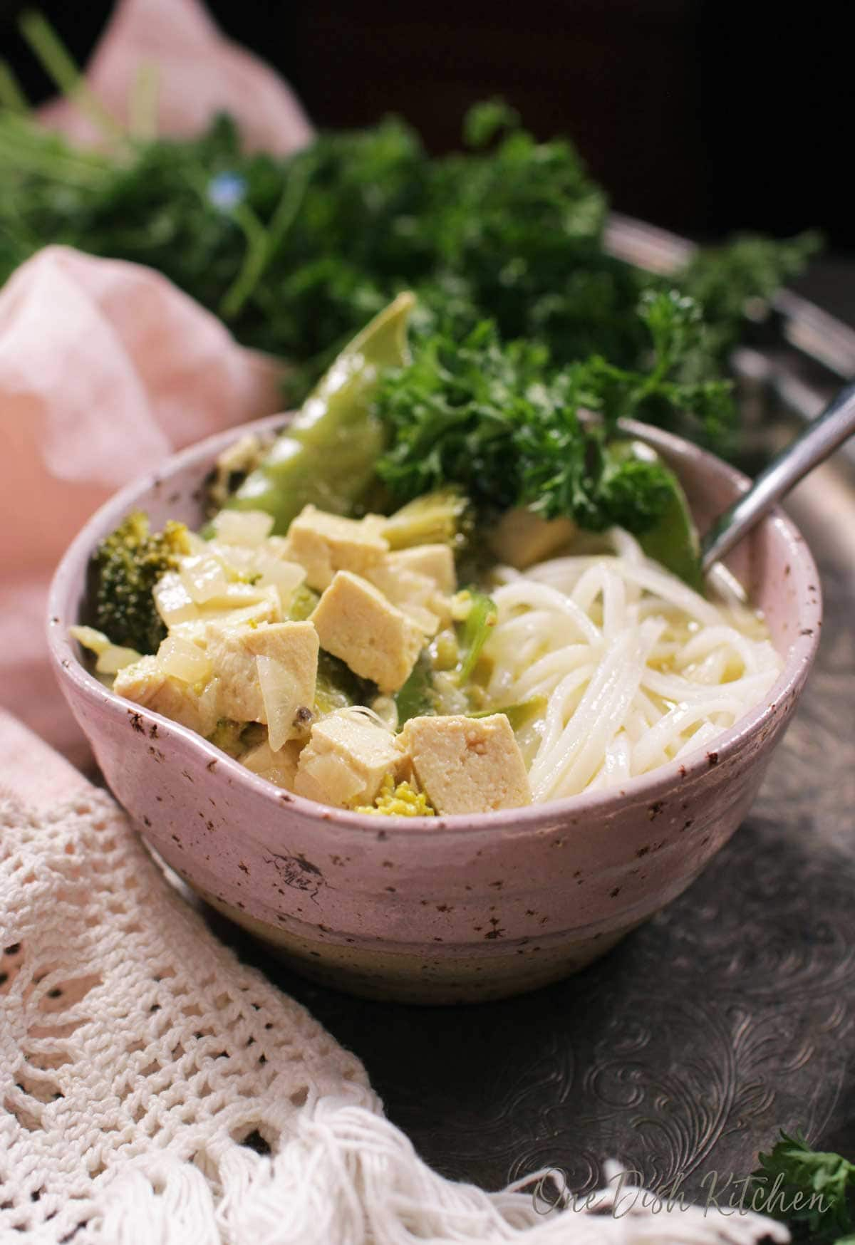A closeup of a bowl of green curry with tofu and noodles on a metal tray  with parsley