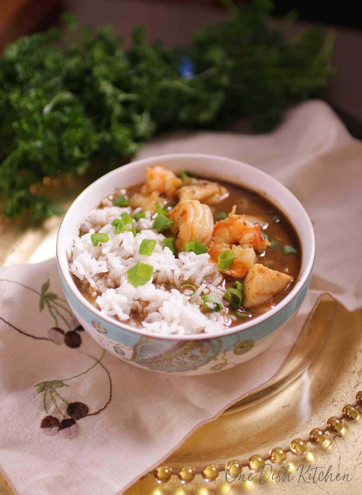 A bowl of gumbo with shrimp and white rice on a tray with parsley in the background.