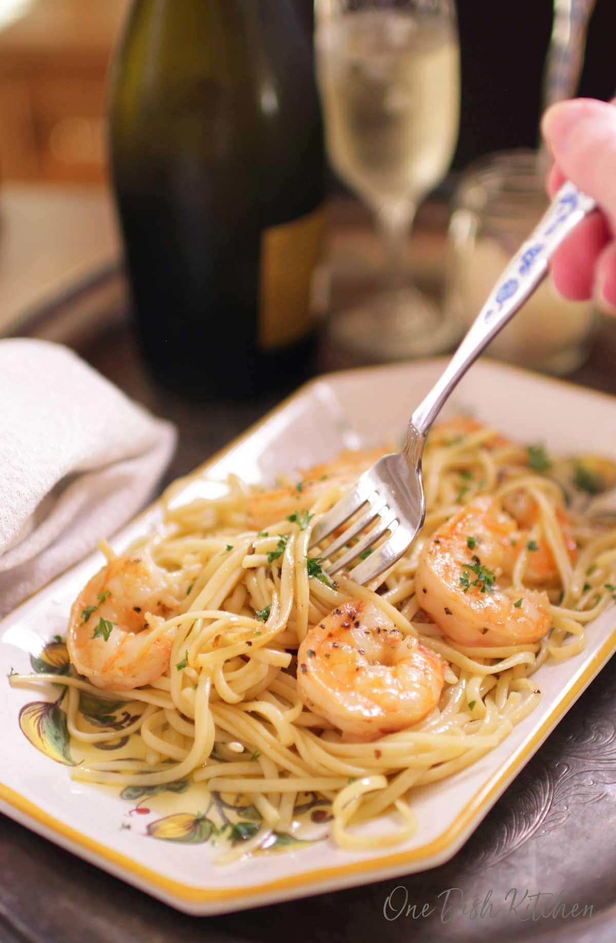 A fork in shrimp scampi on a plate next to a glass of champagne all on a metal tray