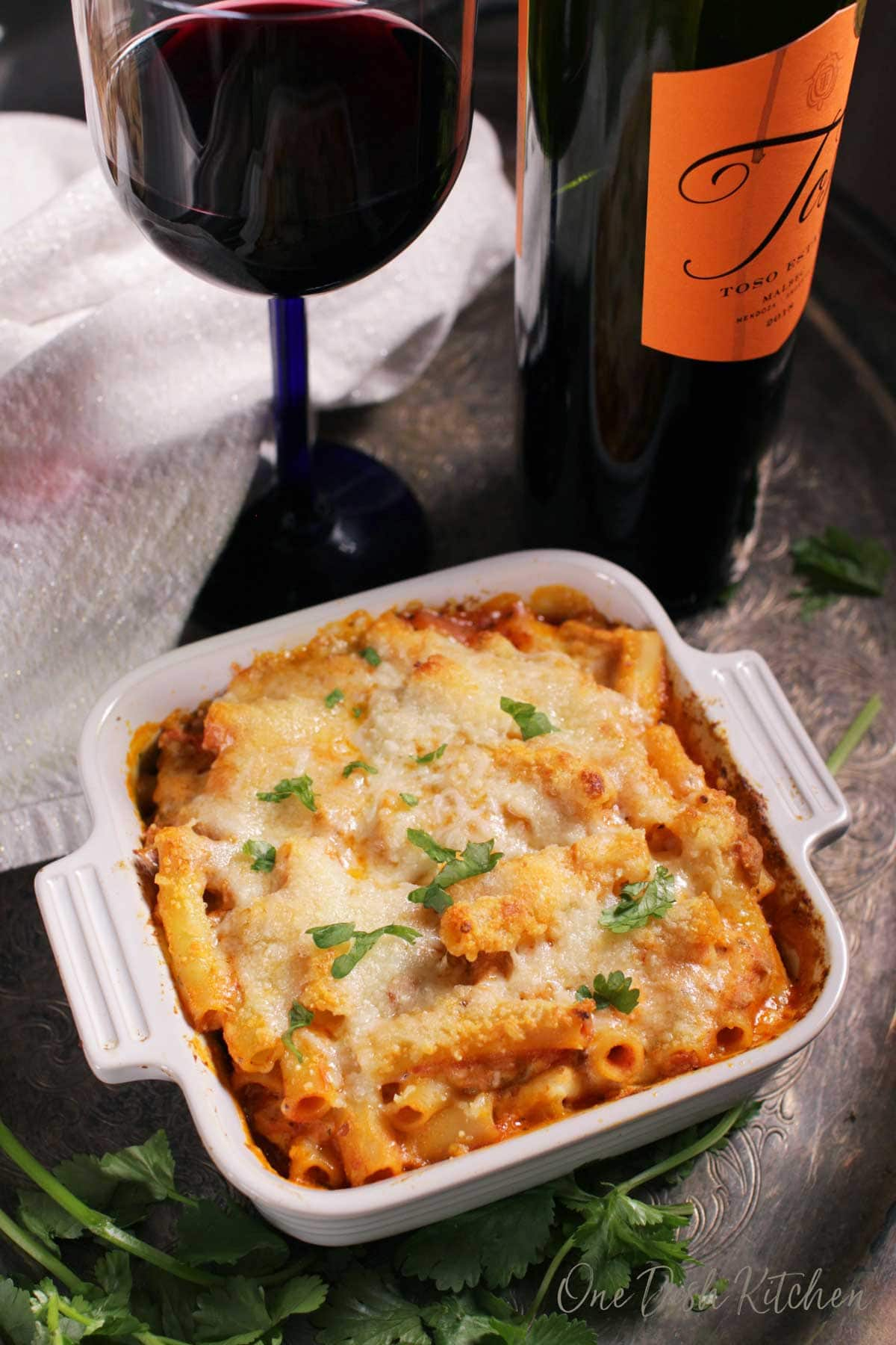 An overhead view of a small baked ziti casserole baked in a small baking dish on a metal tray with a glass and bottle of red wine and parsley