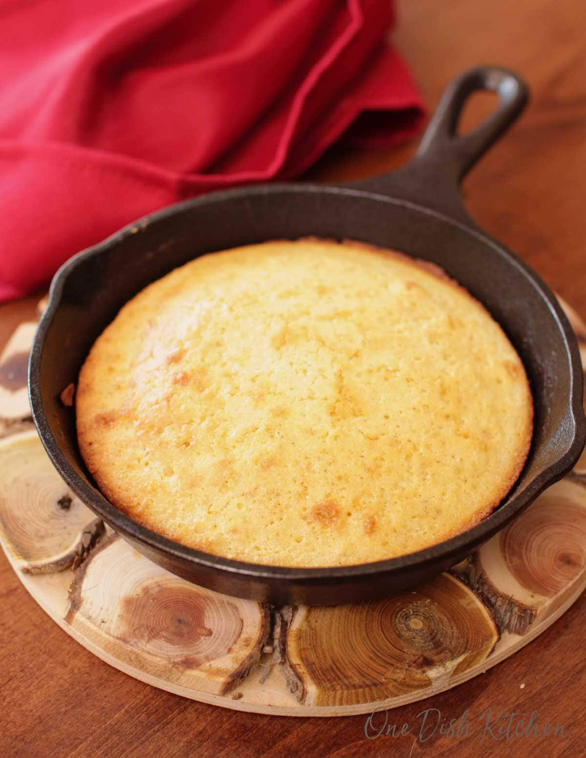 Cornbread in a small cast iron skillet next to a red napkin on a wooden trivet