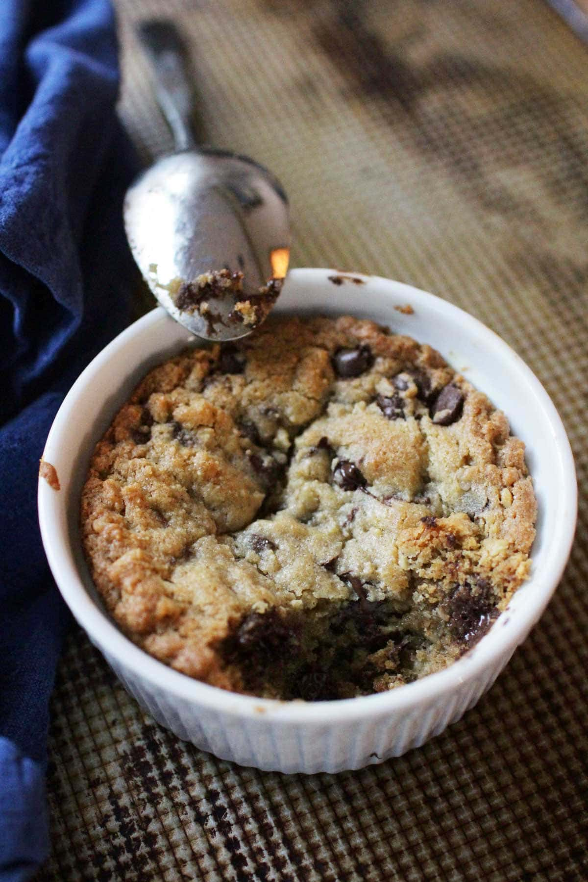 A spoon resting on the edge of a ramekin filled with a deep dish cookie made with chocolate chips