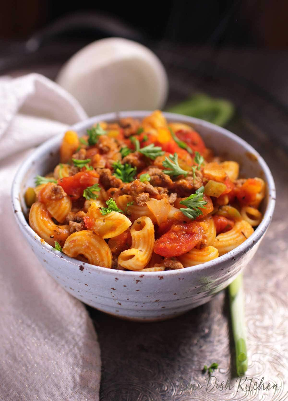 A bowl of american goulash topped with fresh parsley.