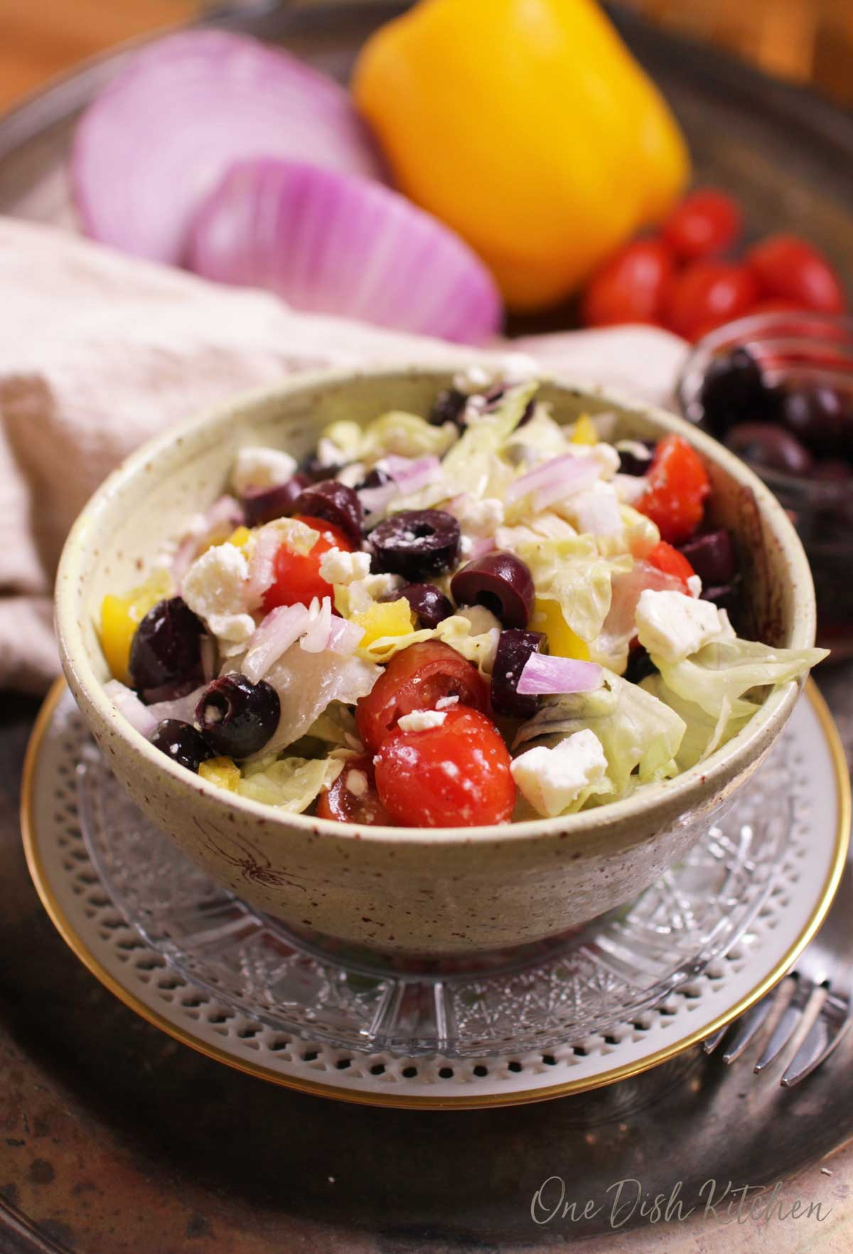 A Greek salad with olives, feta, tomatoes in a bowl with whole vegetables in the background.