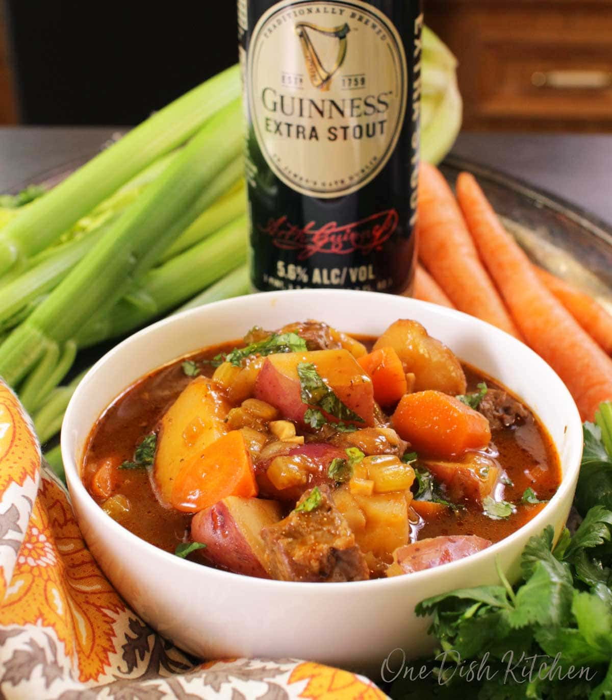 A bowl of irish stew with a can of guinness stout, carrots, and celery in the background.