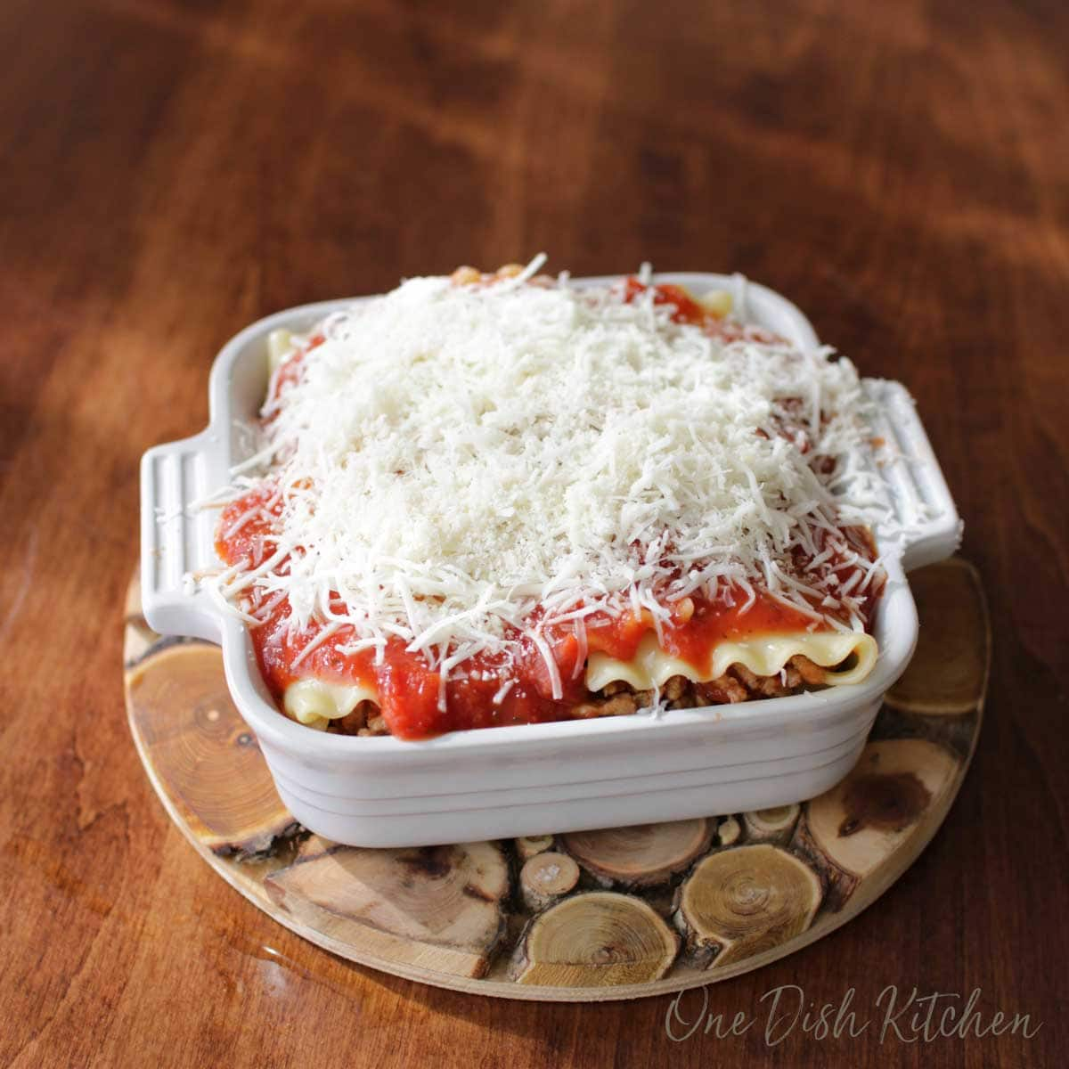 A mini lasagna covered with shredded mozzarella cheese before baking in the oven