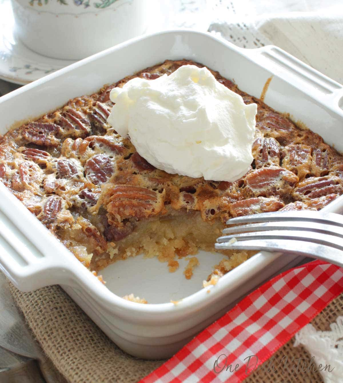 A single serving pecan pie topped with whipped cream and a bite taken out with a fork