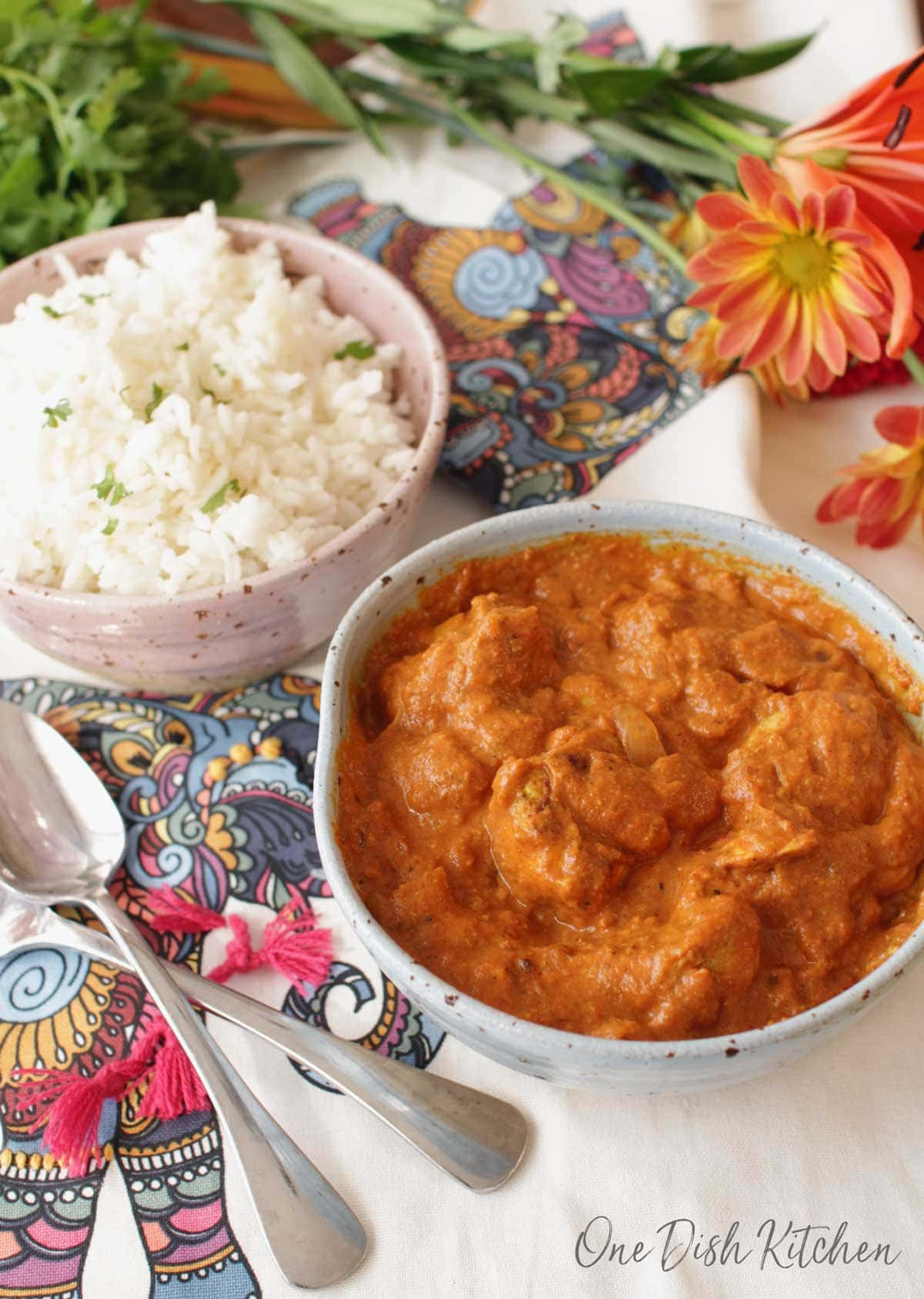 a bowl of butter chicken next to a bowl of white rice on a flowered tablecloth