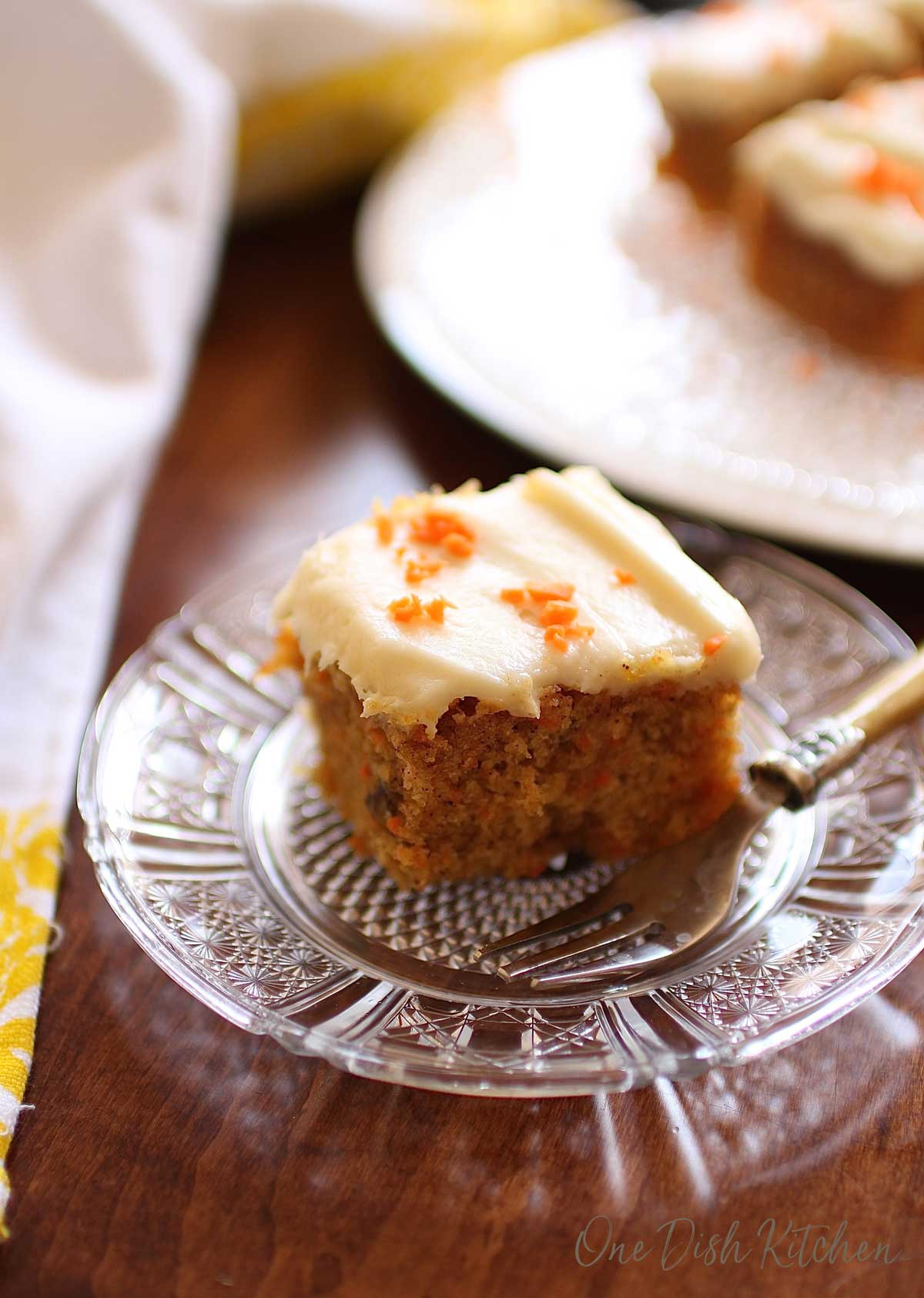 A square slice of carrot cake on a small plate with a fork