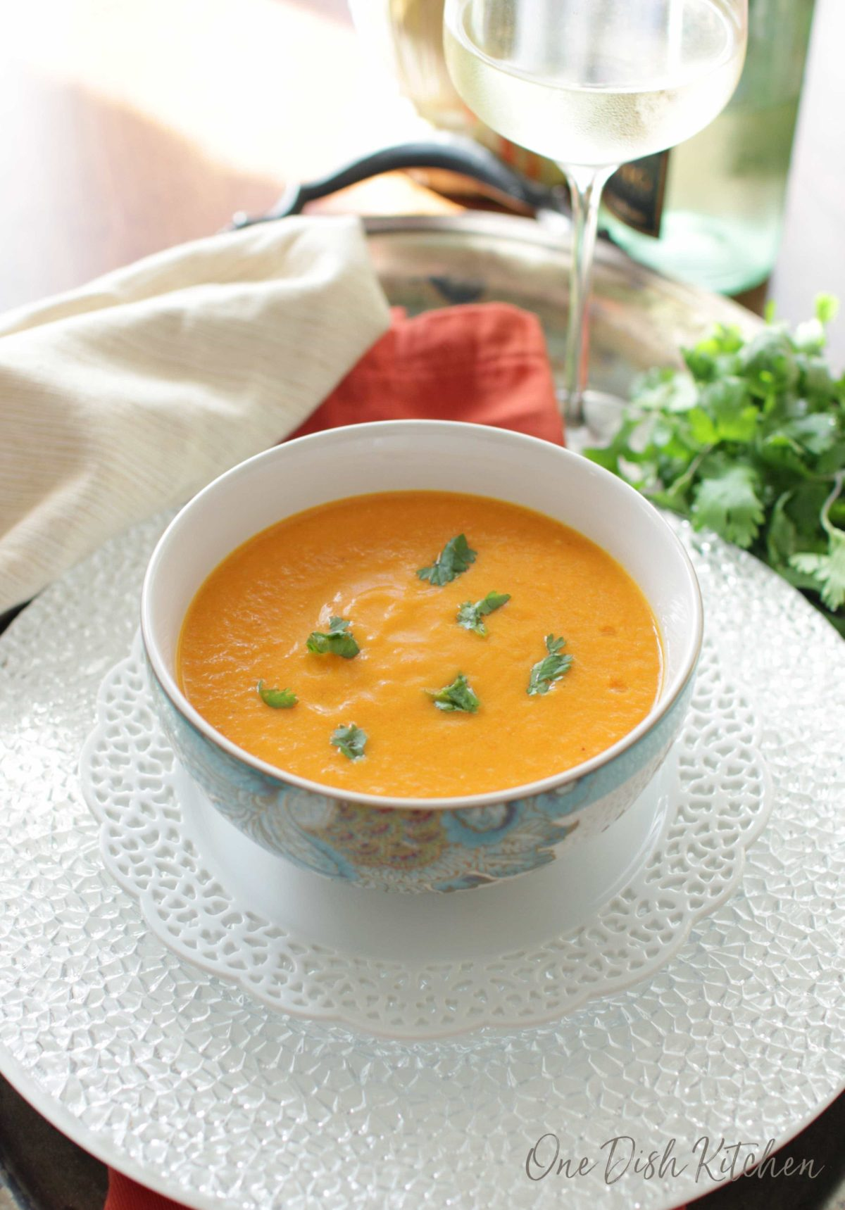 A bowl of carrot soup garnished with cilantro on a glass tray next to a glass of white wine and a bunch of cilantro