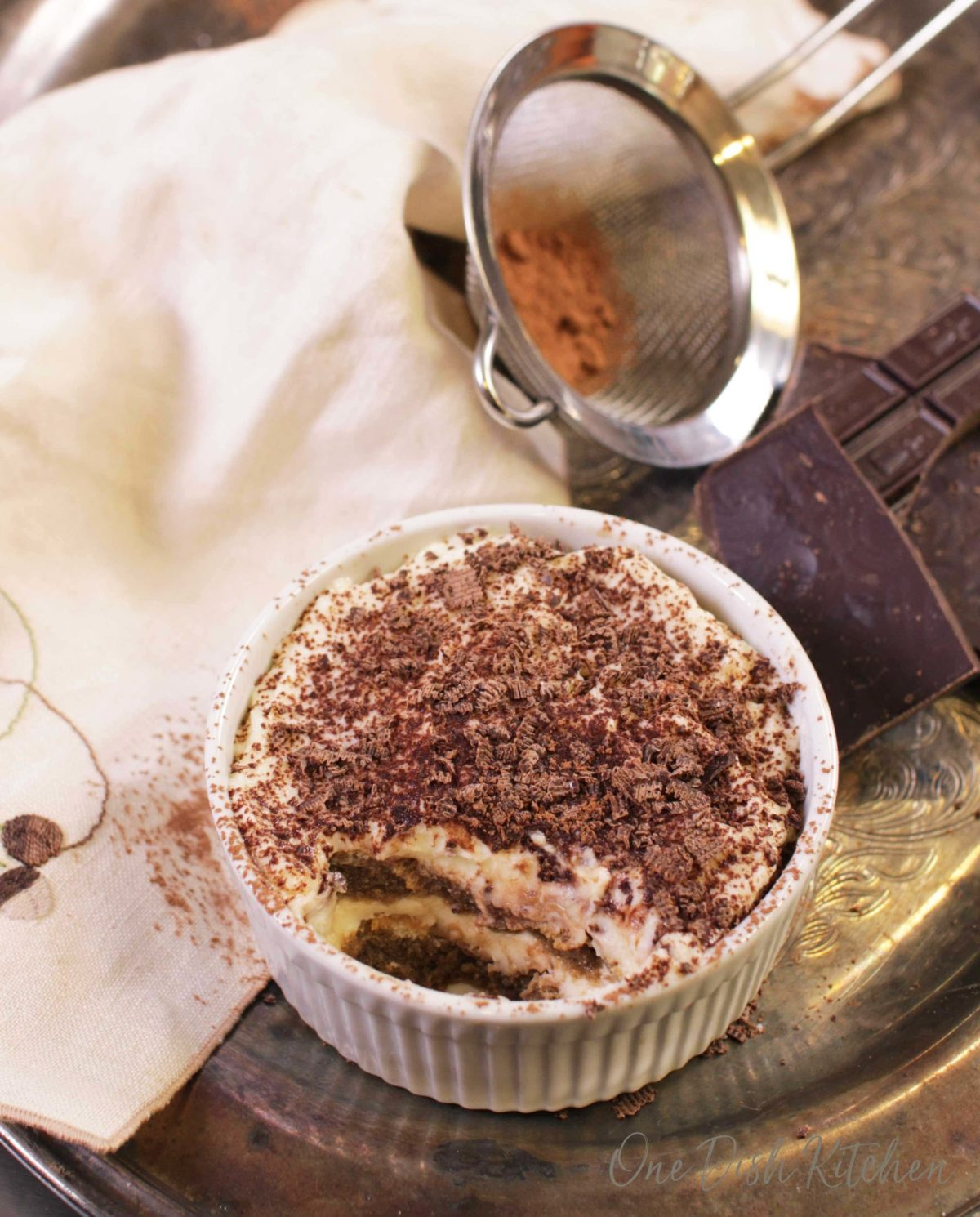 A mini tiramisu topped with chocolate shavings in a ramekin next to a piece of a chocolate bar, a cream-colored cloth napkin, and cocoa powder in a sieve all on a metal tray