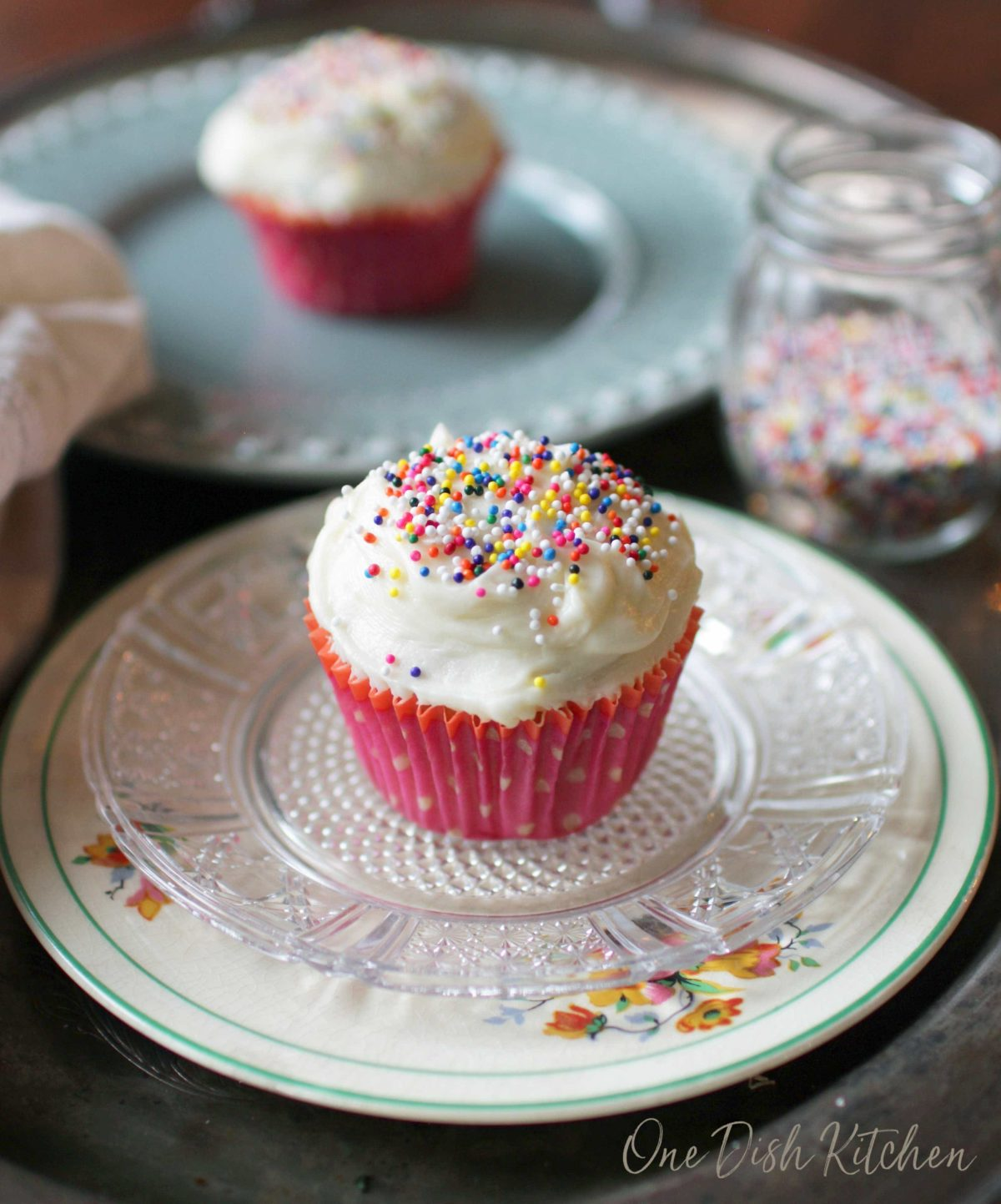 A cupcake with vanilla frosting and rainbow sprinkles on a plate next to another cupcake in the background.