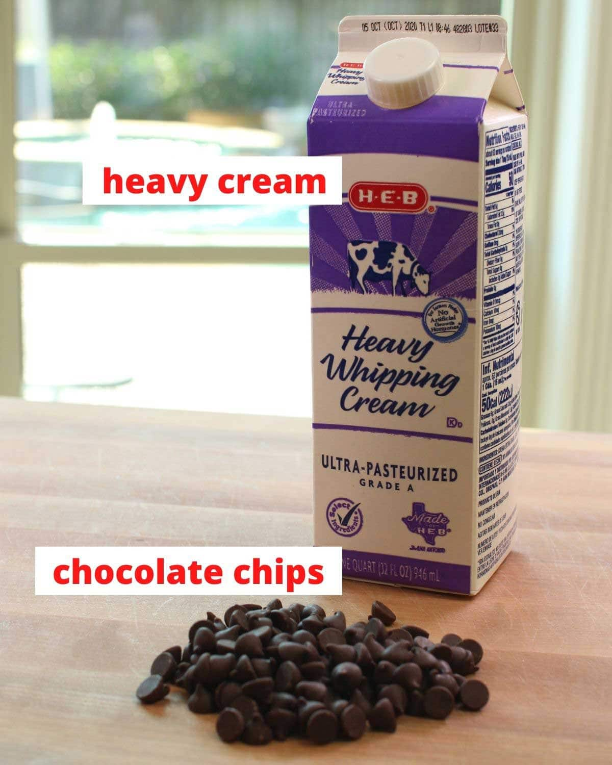 chocolate chips and a carton of heavy cream on a brown cutting board.