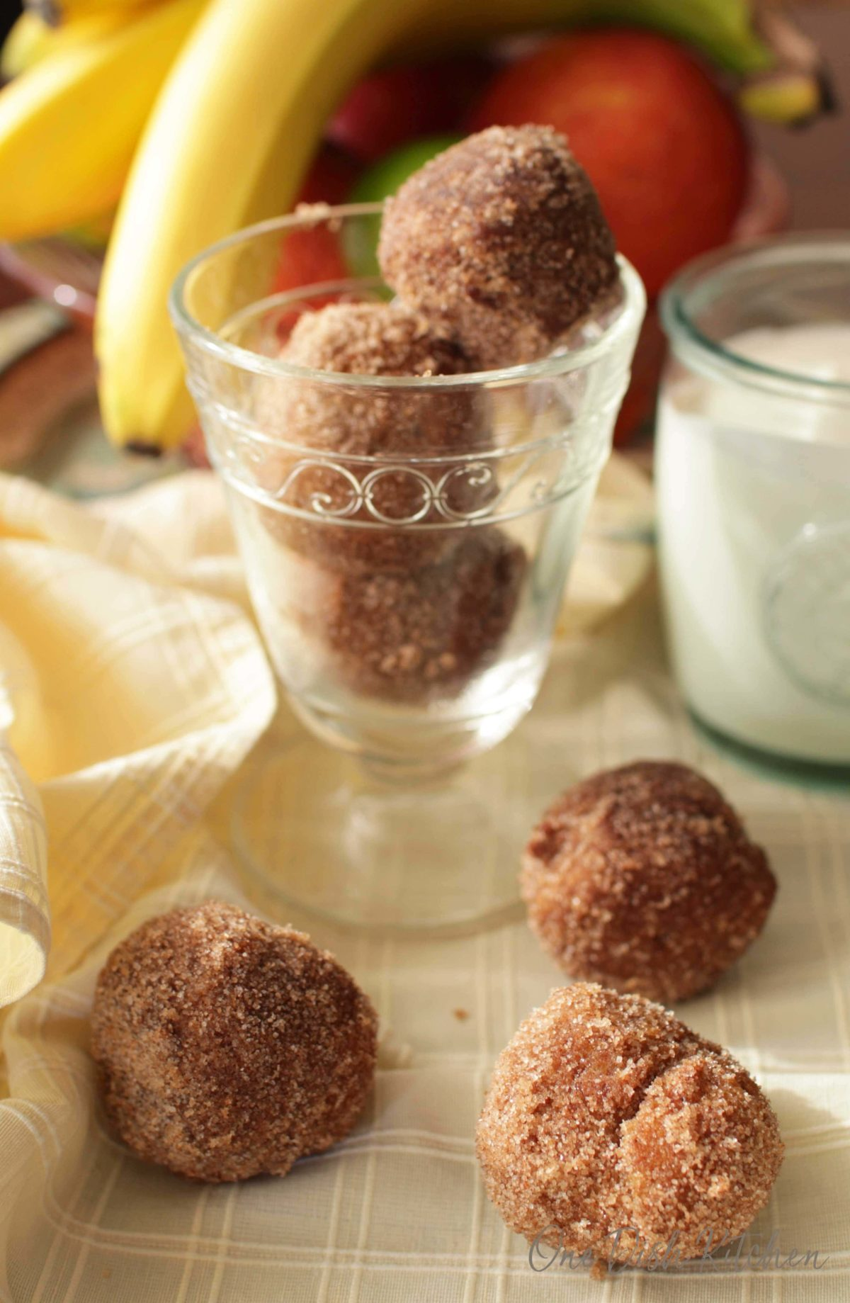 A dessert glass filled with three donut holes next to three donut holes scattered on a cloth napkin all next to a glass of milk