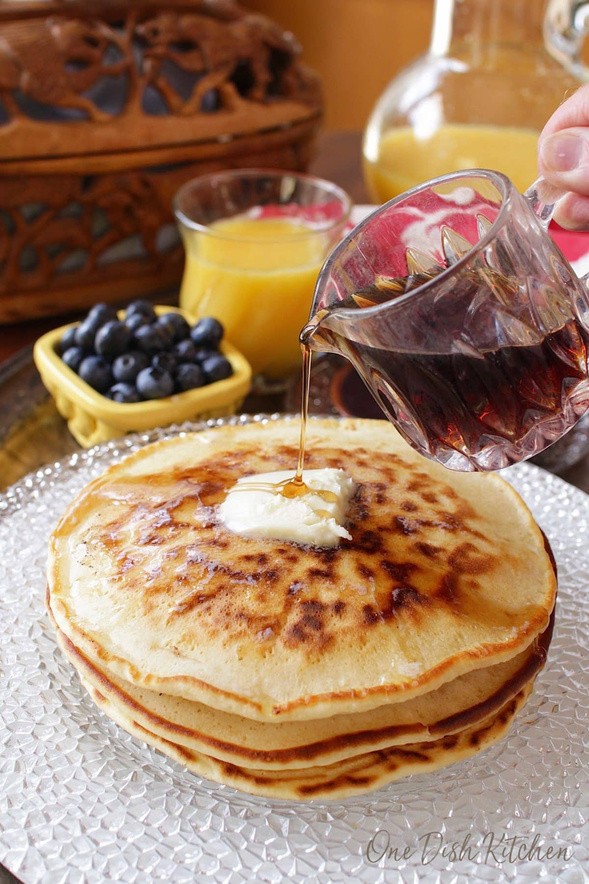 pancakes on a plate with syrup being poured on top.