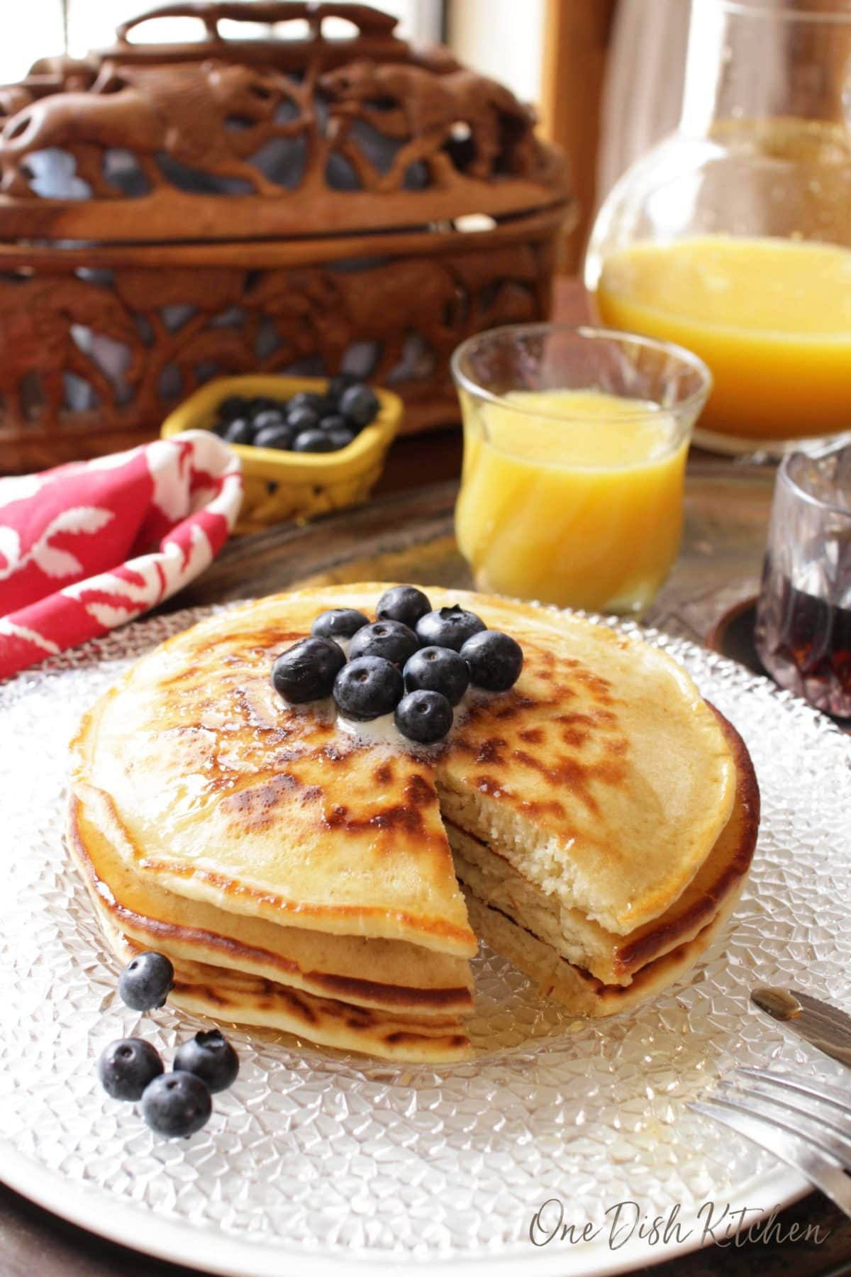 a stack of pancakes topped with butter and fresh blueberries