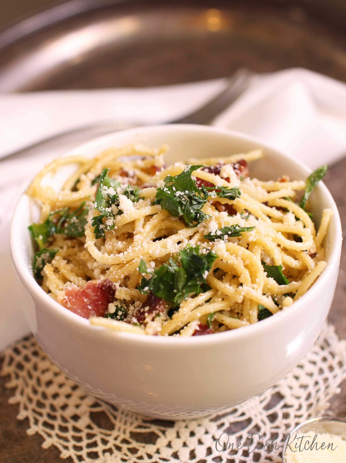 A bowl of pasta carbonara topped with parmesan cheese and parsley on a metal tray.