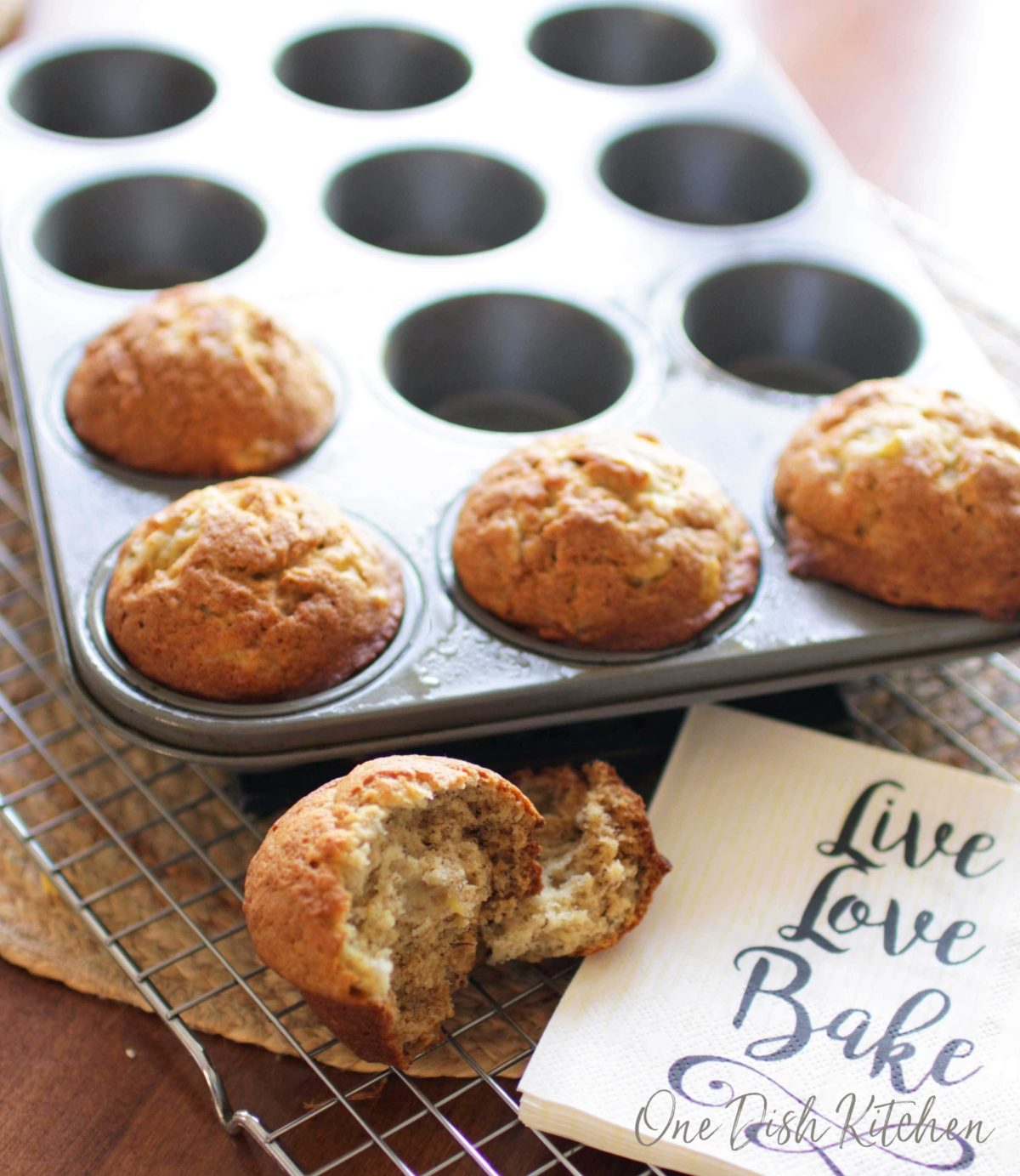 Four banana muffins in a muffin tin and a muffin split in half on a cooling rack