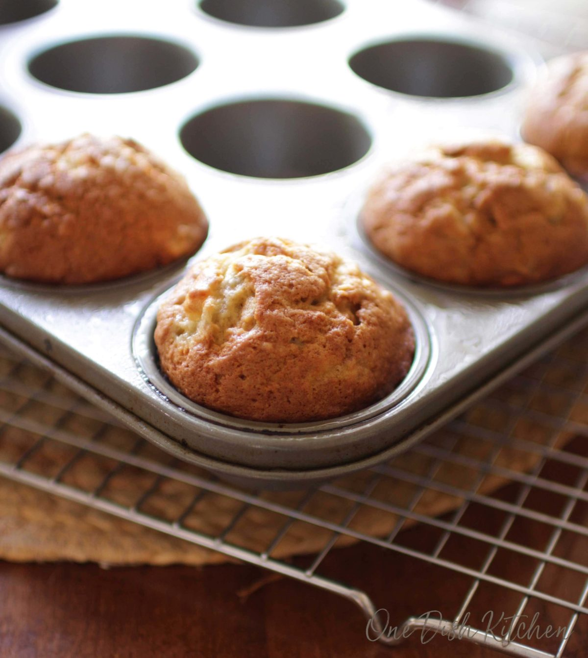 a close up of four banana muffins in a muffin tin