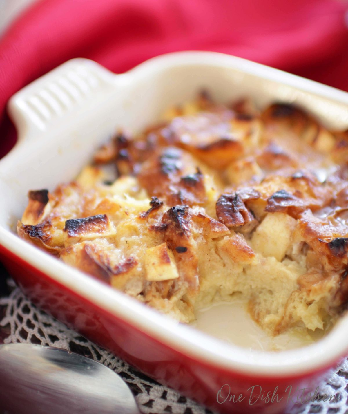 A partially eaten breakfast bread pudding made with bits of croissants on a tray.