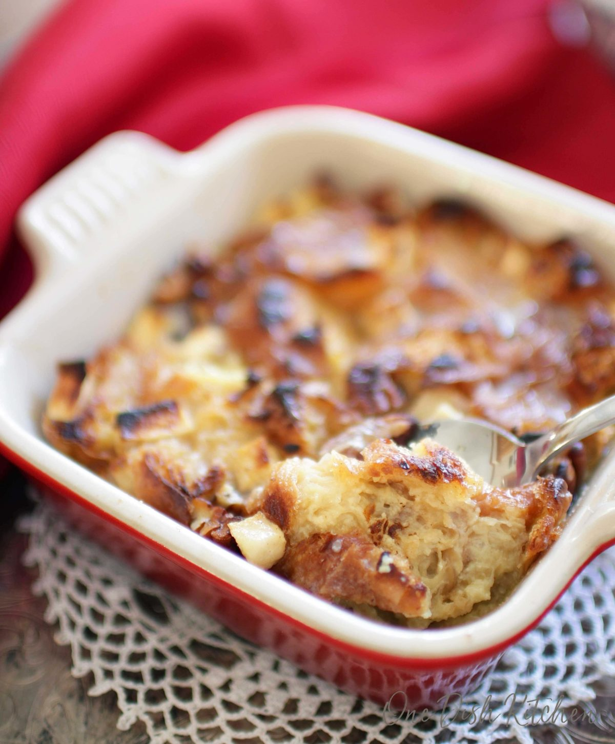 A spoonful of breakfast bread pudding from a small baking dish