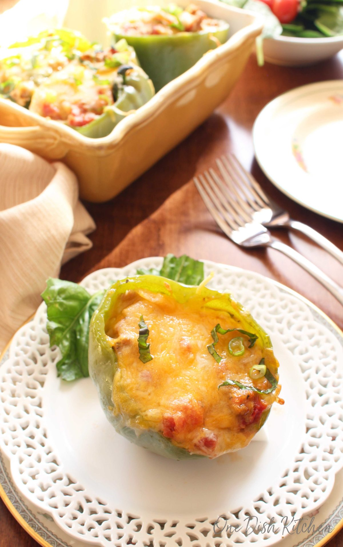 One stuffed bell pepper on a white plate with a yellow dish holding 3 additional stuffed peppers in the background.
